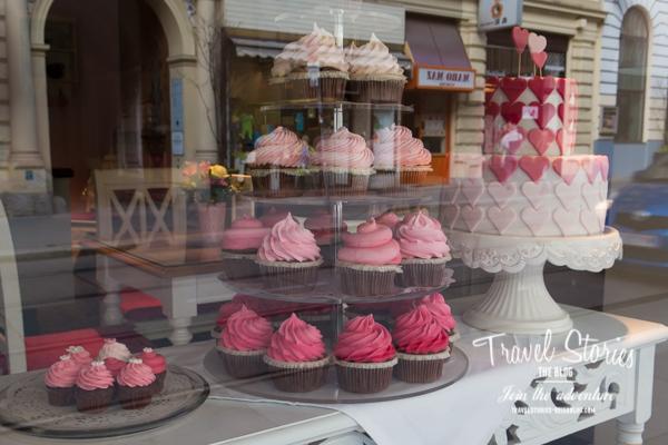 Hochzeitstorte und pinke Muffins im Schaufenster